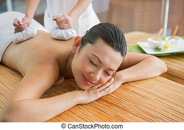 Smiling brunette getting a herbal compress massage at the...