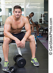 Handsome bodybuilder sitting on bench in weights room at the...