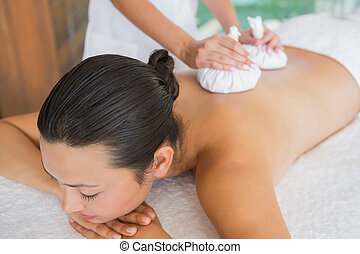 Content brunette getting a herbal compress massage at the...