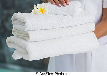 Beauty therapist holding pile of fresh white towels at the...