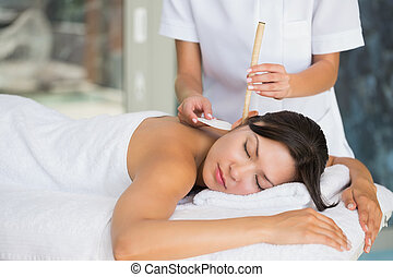 Relaxed brunette getting an ear candling treatment at the...
