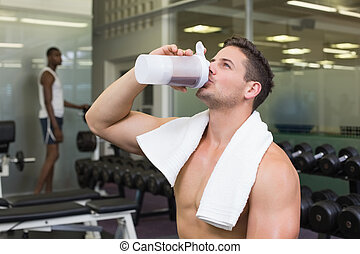 Shirtless bodybuilder drinking protein drink sitting on...