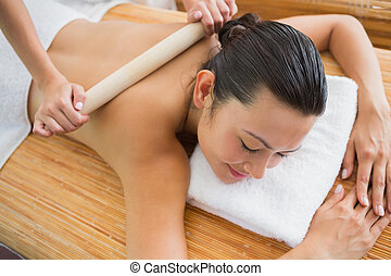 Smiling brunette getting a bamboo massage - Smiling brunette...