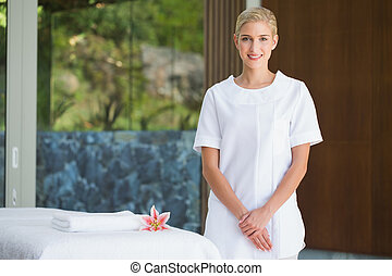 Smiling beauty therapist standing beside massage towel at...