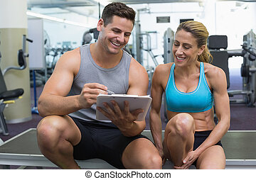 Female bodybuilder sitting with personal trainer talking at...