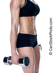 Female bodybuilder working out with large dumbbells mid...