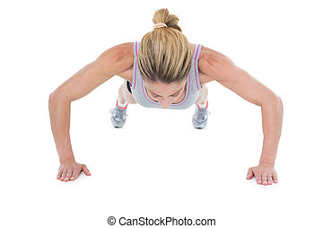 Strong woman doing press ups on white background