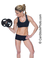 Female bodybuilder holding large black dumbbell with arm up...
