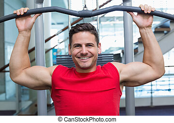 Handsome smiling bodybuilder using weight machine for arms...