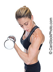Female bodybuilder holding a large dumbbell looking at bicep...