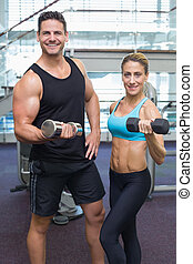 Bodybuilding man and woman holding dumbbells smiling at...