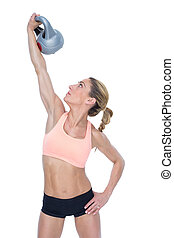 Female blonde crossfitter lifting kettlebell above head on...