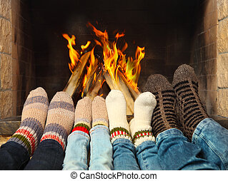 Feet warming near the fireplace - Feets of a family wearing...