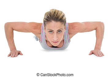 Strong woman doing press ups looking at camera on white...