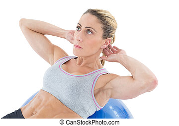 Fit woman doing sit ups on blue exercise ball on white...