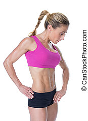 Female bodybuilder posing in pink sports bra on white...