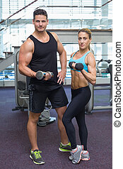 Bodybuilding man and woman holding dumbbells looking at...