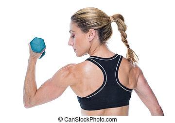 Female bodybuilder holding a dumbbell on white background