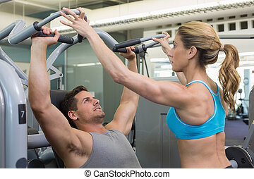 Personal trainer coaching bodybuilder using weight machine...