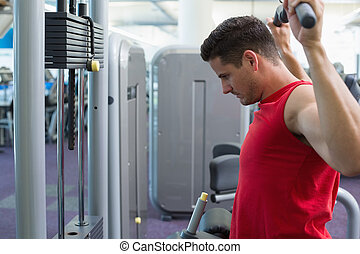 Strong bodybuilder using weight machine for arms at the gym