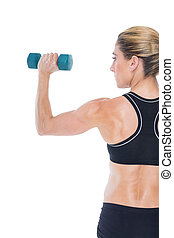 Female bodybuilder holding a blue dumbbell on white...