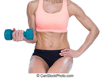 Strong woman doing bicep curl with blue dumbbell on white...