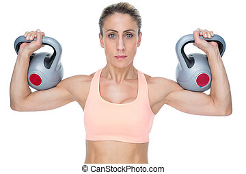 Serious female crossfitter lifting kettlebells looking at...