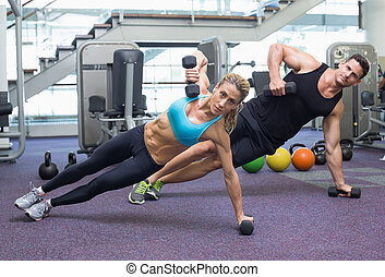 Bodybuilding man and woman holding dumbbells in plank...