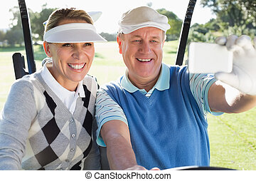 Happy golfing couple sitting in golf buggy taking a selfie...