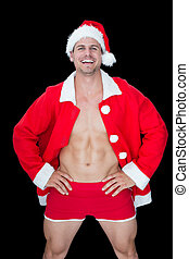 Smiling muscular man posing in sexy santa outfit on black...