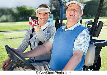 Happy golfing couple sitting in golf buggy looking around on...