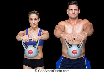 Crossfit couple posing with kettlebells on black background