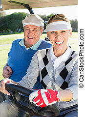 Happy golfing couple sitting in golf buggy smiling at camera...