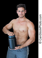 Muscular man posing with nutritional supplement on black...