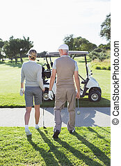 Happy golfing couple walking towards the buggy on a sunny...