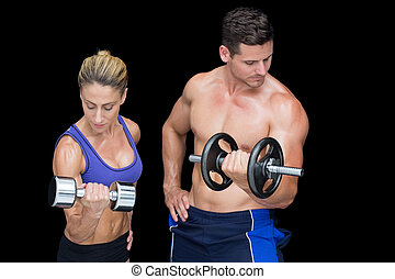 Crossfit couple posing with dumbbells smiling at camera on...