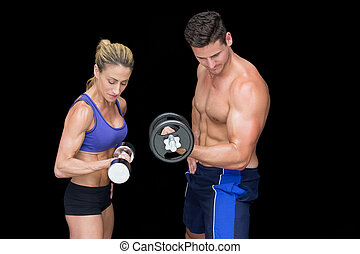Crossfit couple posing with dumbbells on black background