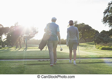 Golfing couple walking and chatting on a sunny day at the...