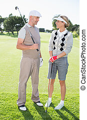 Golfing couple smiling at each other holding clubs on a...