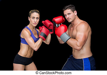 Bodybuilding couple posing with boxing gloves looking at...