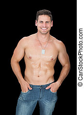 Handsome muscular man posing in blue jeans smiling at camera...