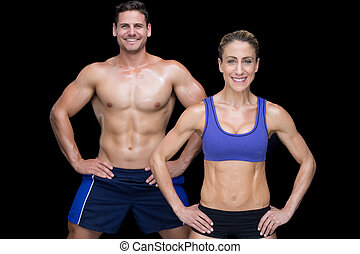Crossfit couple smiling at camera with hands on hips on...
