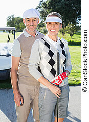Happy golfing couple looking at camera with golf buggy...