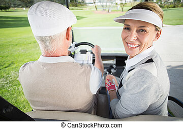 Golfing couple driving in their golf buggy with woman...