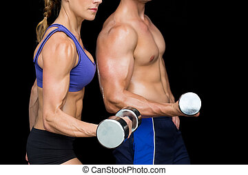 Bodybuilding couple posing with large dumbells on black...