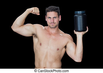 Happy muscular man posing with nutritional supplement on...