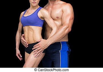 Fit bodybuilding couple posing together on black background
