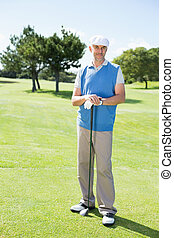 Cheerful golfer smiling at camera holding his club