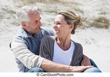 Attractive couple smiling at each other on the beach on a...