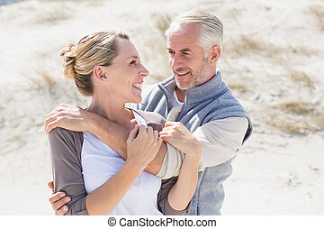 Happy hugging couple on the beach looking at each other